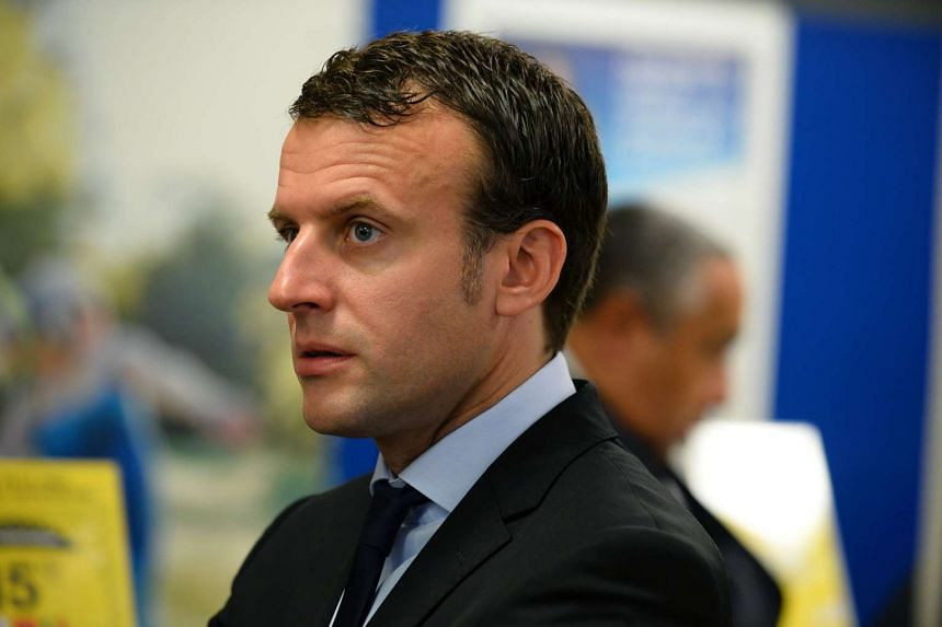 French economy minister Emmanuel Macron stands inside the Post Office to unveil a stamp in Montreuil after protesters threw eggs on his head, on June 6, 2016.