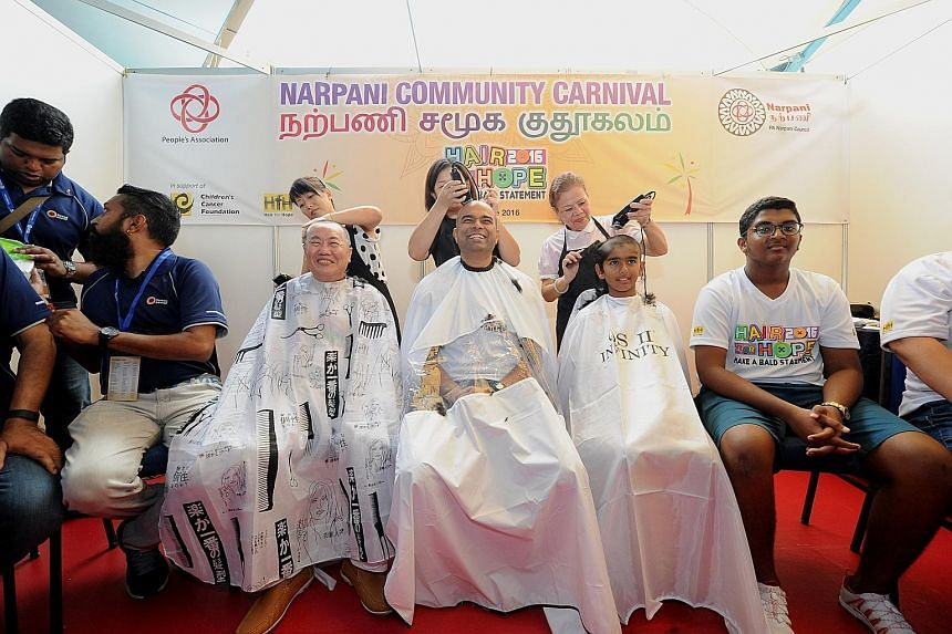 Dr Janil Puthucheary (centre) getting his head shaved for a good cause. Joining him are retiree Teo Jing Teng and student Pranav Srinivasan.