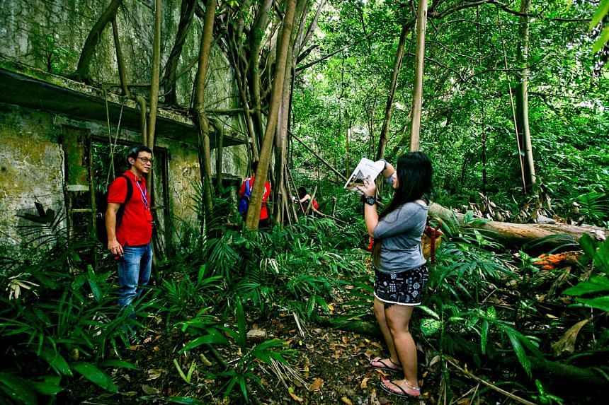 Heritage trail walkers at a wooded area in Kay Siang Road, where the remnants of two long-abandoned storage bunkers lie.