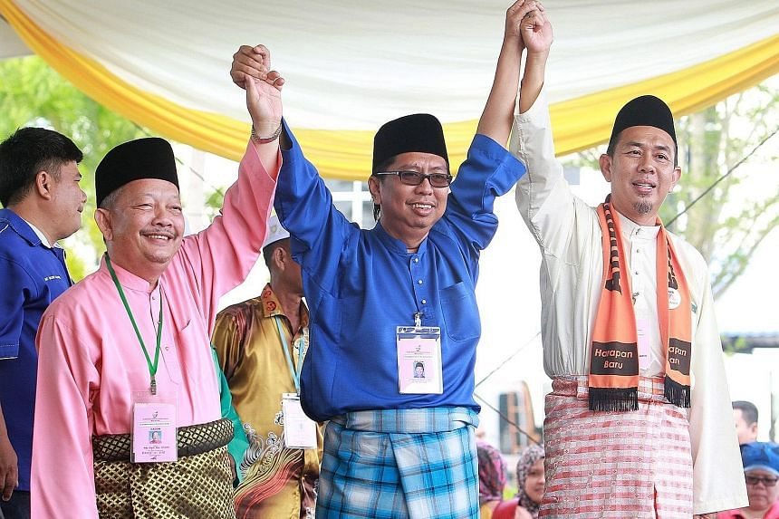 (From left) PAS candidate Abdul Rani Osman, BN candidate Budiman Mohd Zohdi and Amanah candidate Azhar Abdul Shukur sharing a light moment yesterday at the Sungai Besar nominations at Dewan Seri Bernam. The fight there is expected to be close as Umno