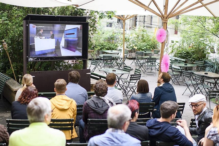 People watching the first projections of the referendum results in Bern yesterday. The proposal sought to introduce a monthly income of 2,500 Swiss francs (S$3,500) per adult and 625 francs per child under 18 no matter how much they work.
