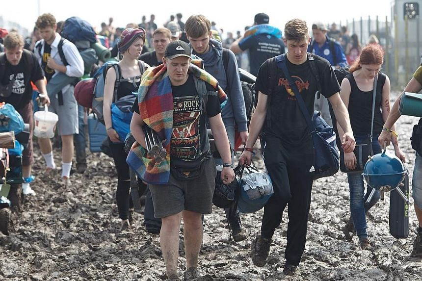 Fans wading through thick mud on the grounds of the Rock am Ring festival in Mendig, Germany, on Saturday. The festival was cancelled after some 80 people were hurt due to lightning strikes.