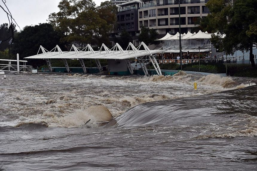 A Sydney ferry terminal submerged by floodwaters after the freak storm struck yesterday. High winds forced Sydney Airport to close two of its three runways.