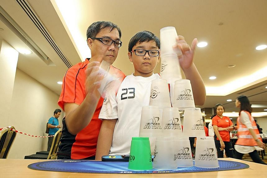 """Mr Steve Tubao and his son Paul taking part in the World Sport Stacking Association 2016 Singapore Open held at the Orchid Country Club over the weekend. Mr Tubao also formed a pair with his daughter, Mary. Both pairs won in their """"doubles"""" segments"""