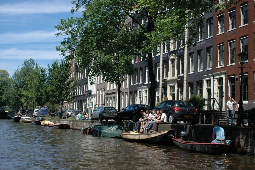 People sitting at a canal in Amsterdam, The Netherlands.