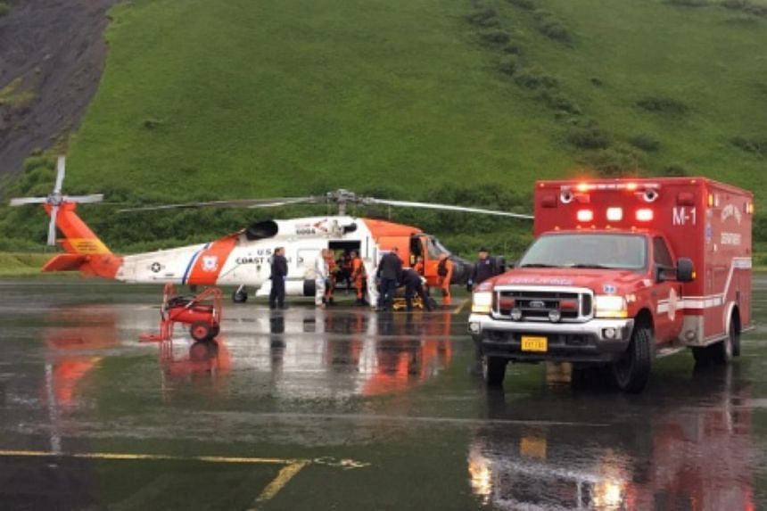 Emergency medical personnel transfer patients from a rescue helicopter to an ambulance.