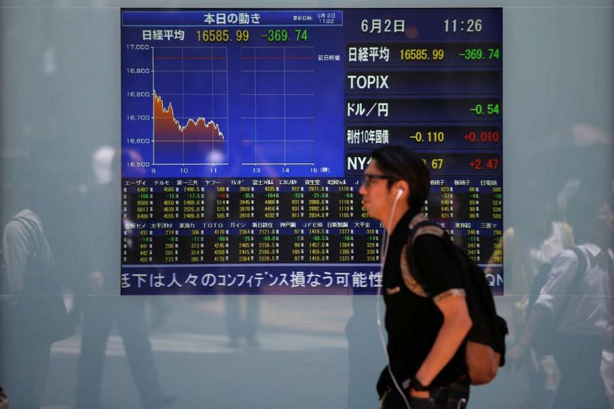 A man walks in front of a screen showing Nikkei share average outside a brokerage in Tokyo, Japan, June 2.