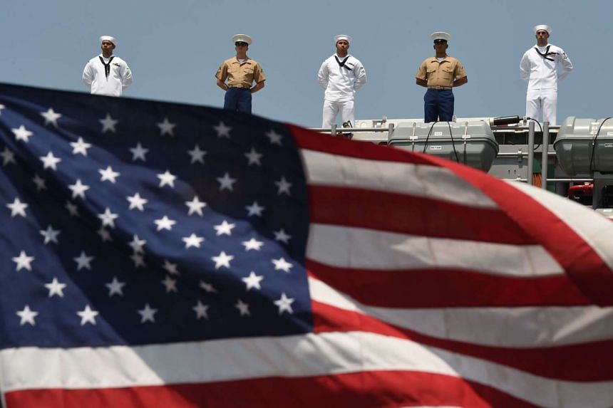 US sailors and marines standing on the deck of a ship.