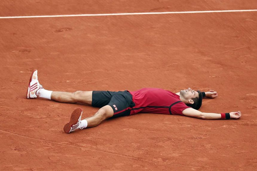 Djokovic celebrates after winning the French Open title for the first time.
