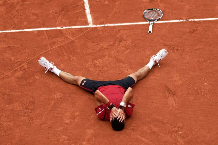 Djokovic covers his face in disbelief after finally winning his first French Open.