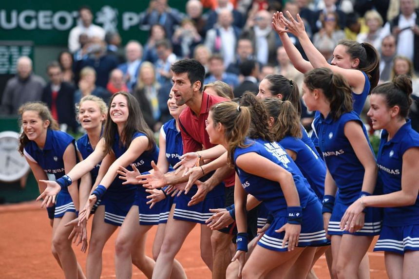Djokovic gestures flanked by ball girls after winning the men's final match at Roland Garros.
