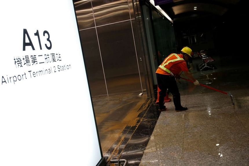 A worker sweeps water out during a partial power failure after heavy rain caused flooding at Taoyuan International Airport, Taiwan on June 2.