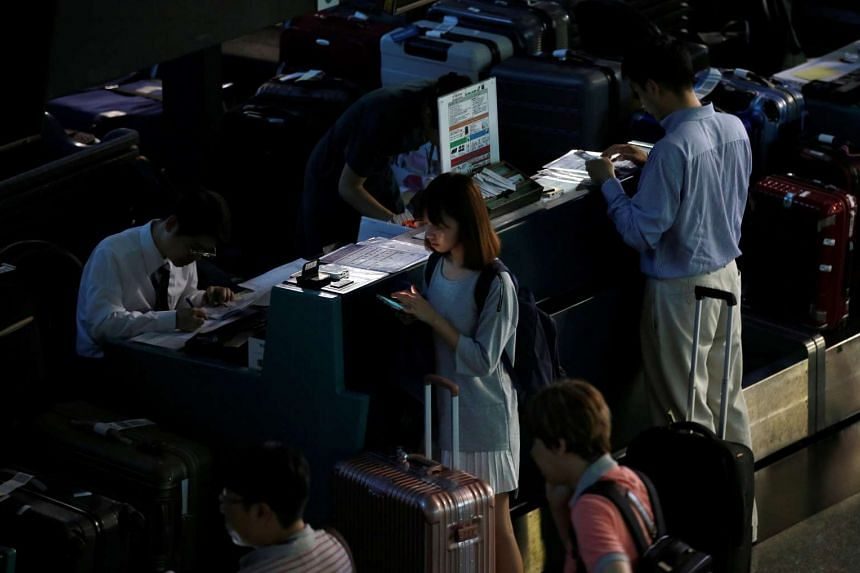 Passengers wait at the check-in counter in the dark during a partial power failure after heavy rain caused flooding at Taoyuan International Airport, Taiwan on June 2.