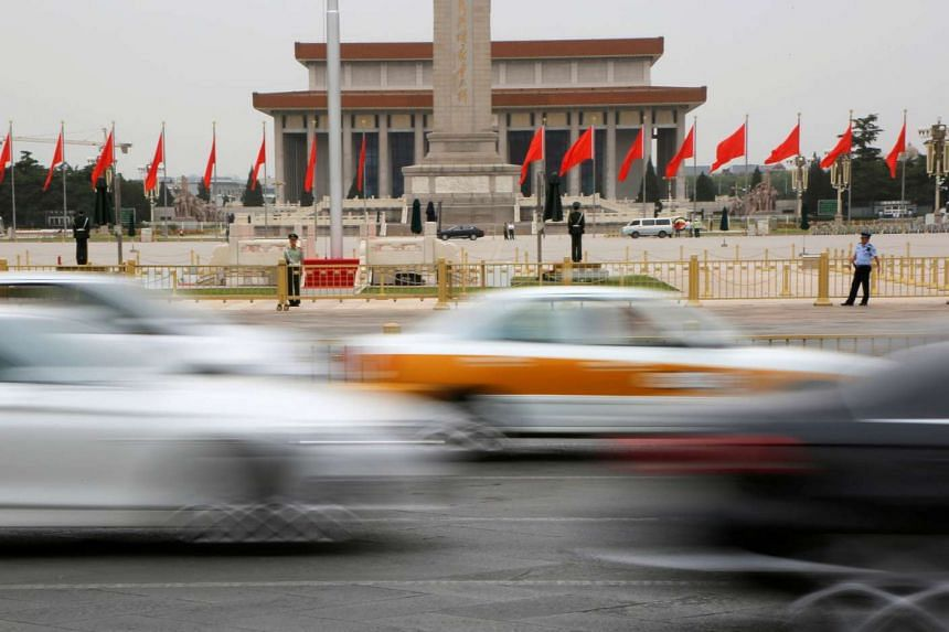 Cars pass by the Mausoleum of the late Mao Zedong and the Monument to the People's Heroes at Tiananmen Square in Beijing, on May 31, 2016.