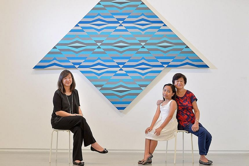 Anthony Poon's family - (from far left) daughter Poon Siew-Win, nine-year-old grand-daughter Emma Lim and wife Tan Lee Lee - in front of an untitled acrylic on canvas painting that is part of the artist's Kite series.