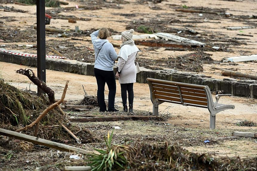 People inspecting the damage caused by the storm at the beachside suburb of Collaroy in New South Wales. Further flooding and erosion are expected after an abnormally high tide hit the state last night. A helicopter search and rescue operation being