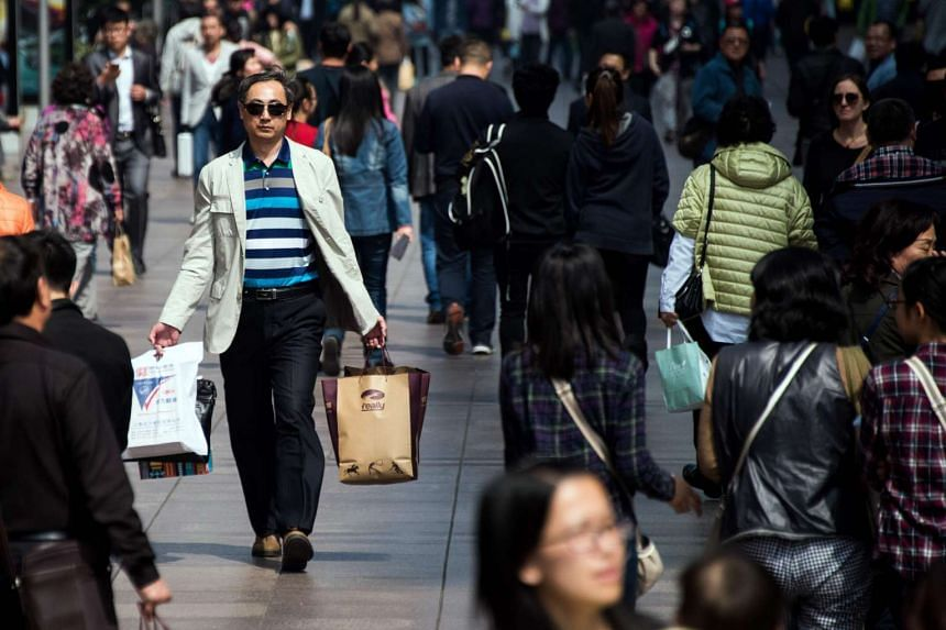 A man carries his shopping bags on a busy street in Shanghai on April 1.