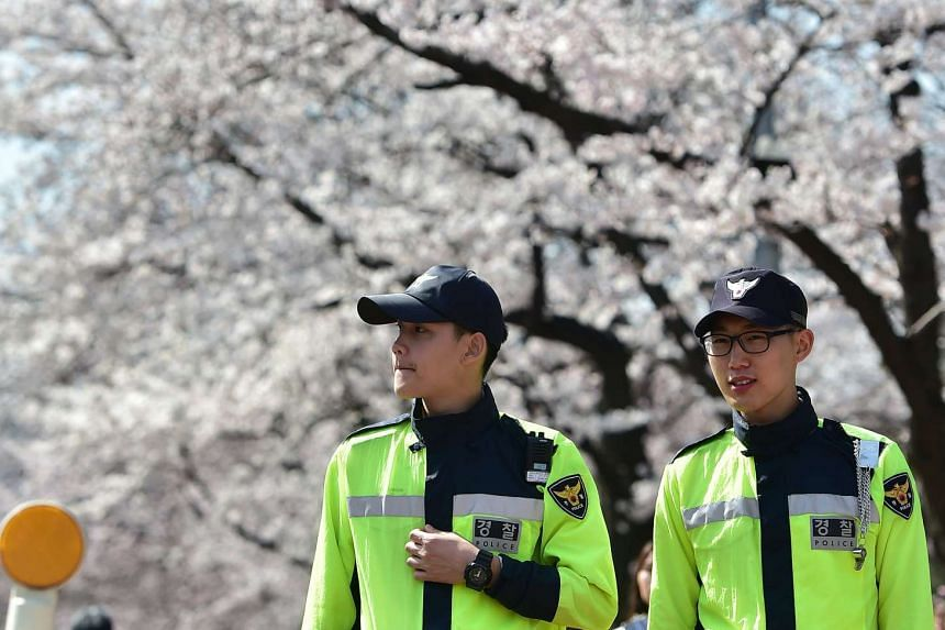 South Korean policemen patrolling under cherry blossoms near the national assembly in Seoul on April 4, 2016.