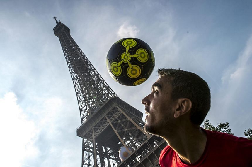 A young man shows his football skills in front of the Eiffel Tower in Paris, France on June 6.