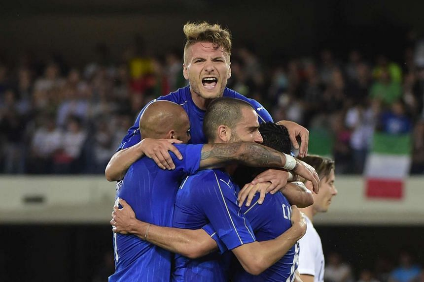 Italy's Antonio Candreva (right) celebrating with teammates Ciro Immobile (top) and Leonardo Bonucci (centre) after scoring a penalty against Finland.