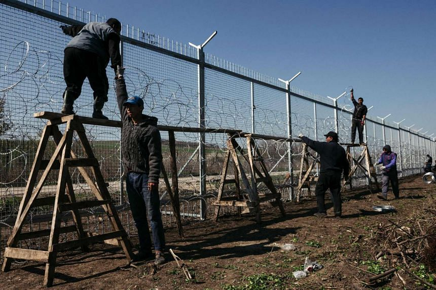 Workers attach barbed wire to a border fence to prevent illegal crossings by migrants at the Bulgarian-Turkish border near the Bulgarian village of Shtit, on March 18, 2016.