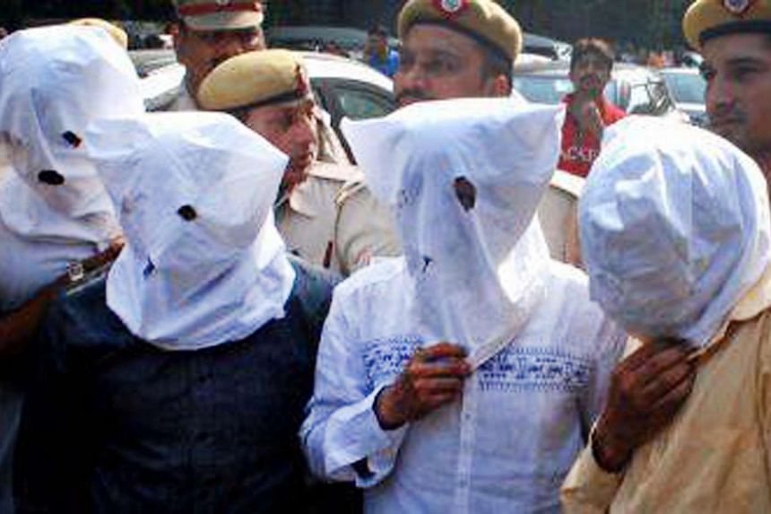 Suspected members of an organ trafficking gang wearing masks after their arrest in New Delhi.