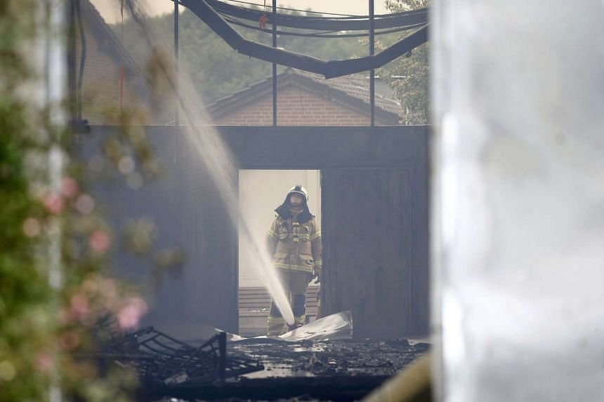 A firefighter extinguishes a fire at an exhibition hall used as a refugee camp in Duesseldof, Germany, on June 7, 2016. PHOTO: REUTERS