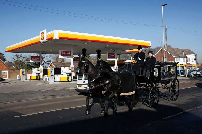 A horse-drawn funeral carriage passing a Royal Dutch Shell petrol station in Hook, near Basingstoke, on Jan 20, 2016.