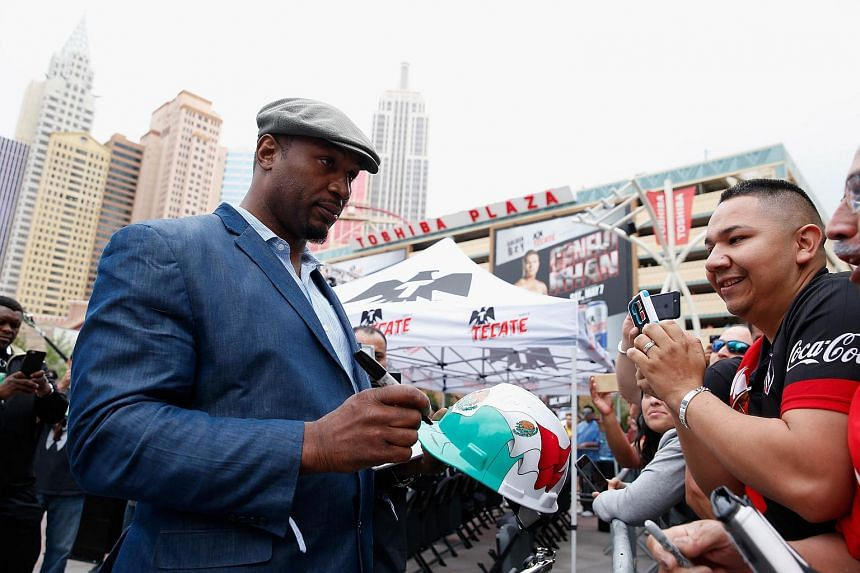 Retired boxer Lennox Lewis (left) signs autographs for fans on May 6 in Las Vegas, Nevada.