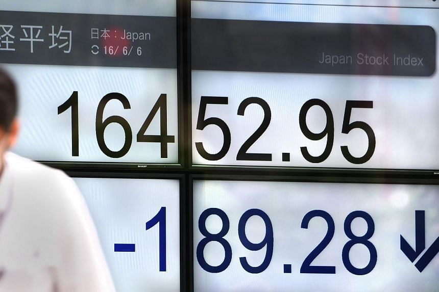A man walks past the Nikkei key index of the Tokyo Stock Exchange in front of a securities company in Tokyo on June 6.