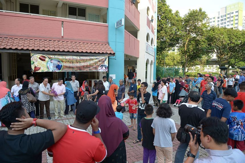 Sembawang GRC MP Mr Amrin (wearing a pink shirt and holding a plastic bag of food) distributing rice and porridge to needy residents in Woodlands yesterday to mark the start of a grassroots charity project. Mr Amrin said the initiative aims to replicate t