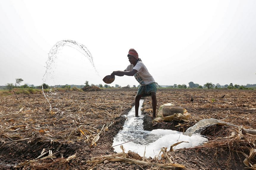 A farmer throwing water after making a canal to irrigate his field in Kolkata, India, last month. Agriculture consumes 83 per cent of India's national freshwater resources as the country strives to feed a huge population, of which more than 15 per cent is