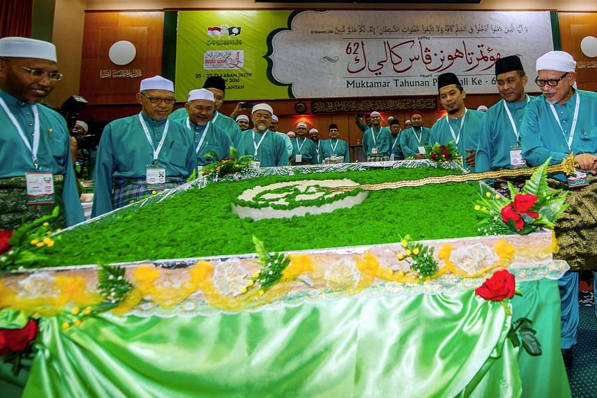 PAS president Abdul Hadi Awang (right) cutting a cake to open the PAS annual congress at Pengkalan Chepa in Kelantan last Thursday. Recent developments do not mean PAS will ally with Umno before the next general election. They only show that PAS has not c