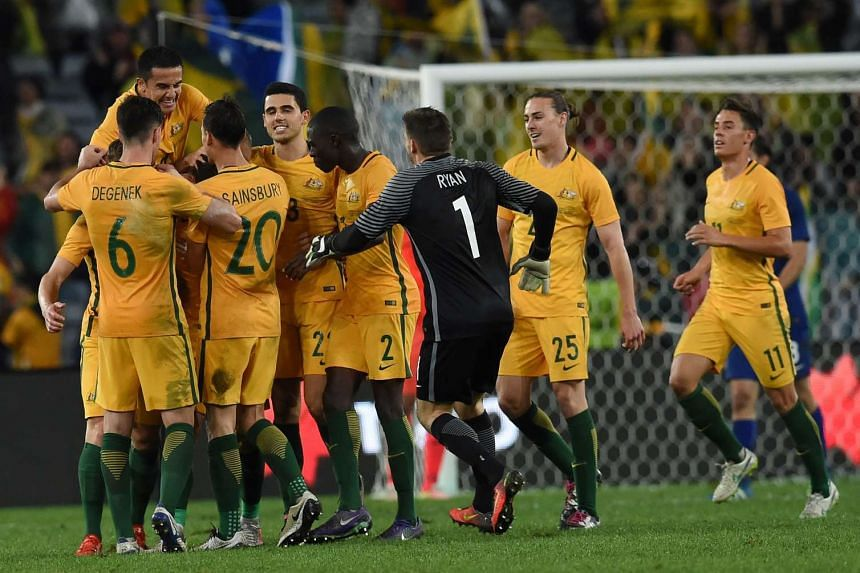 Australia's players celebrate a goal against Greece during their international friendly football match in Sydney on June 4, 2016.