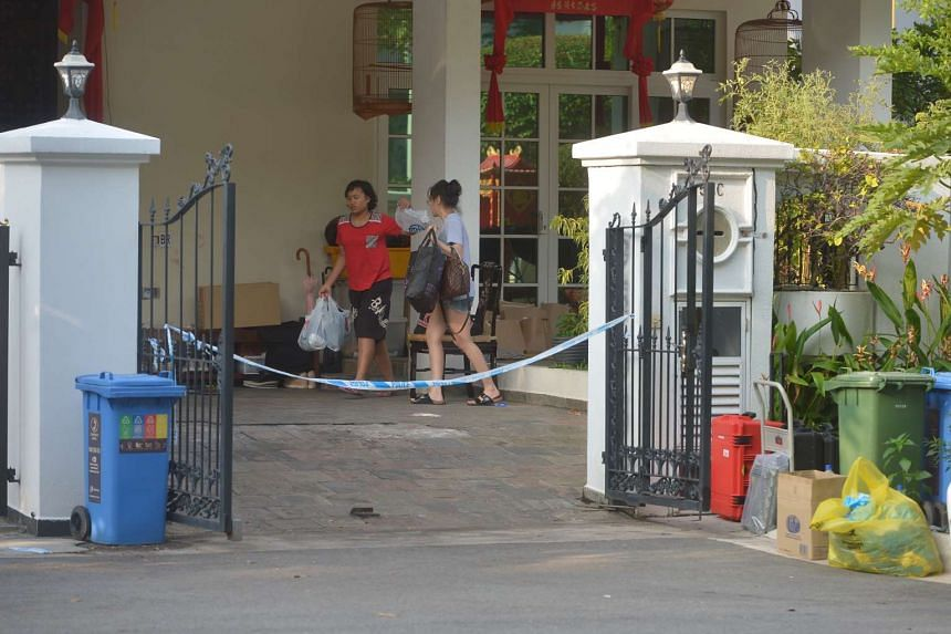 A lady and one of the maids (in red) clearing items off the porch at 50C Lorong H Telok Kurau on June 8, 2016.