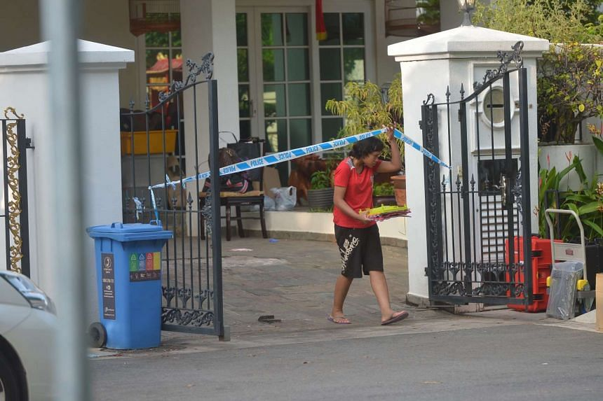 One of the maids (in red) clearing items off the porch at 50C Lorong H Telok Kurau on June 8, 2016.