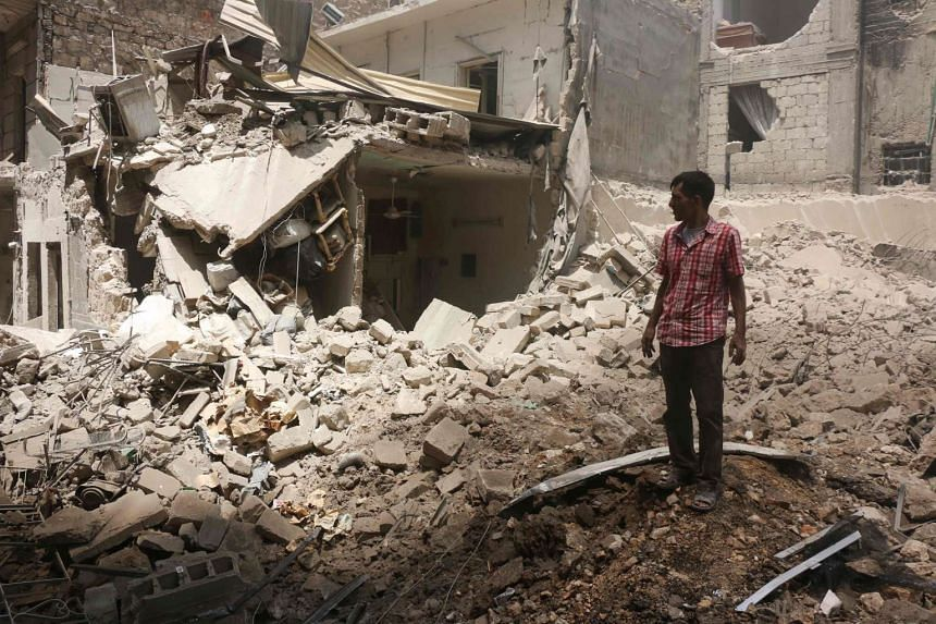 A man stands on the rubble of a destroyed building following reported air strikes by government forces in the rebel-held Shaar neighbourhood in Aleppo on June 8, 2016.