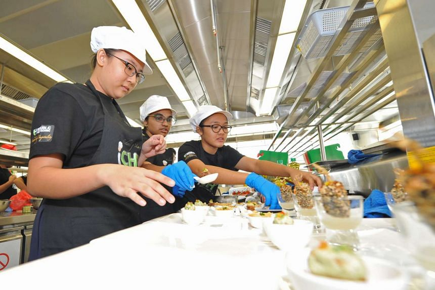 (From left) Geraldine Kang Him Hong, Tara Laxmi Prasob and Amirah Sabrina Bte Fathurrahman from Junyuan Secondary School preparing their canapes for judging at the Republic Polytechnic iChef Challenge 2016 Finals.