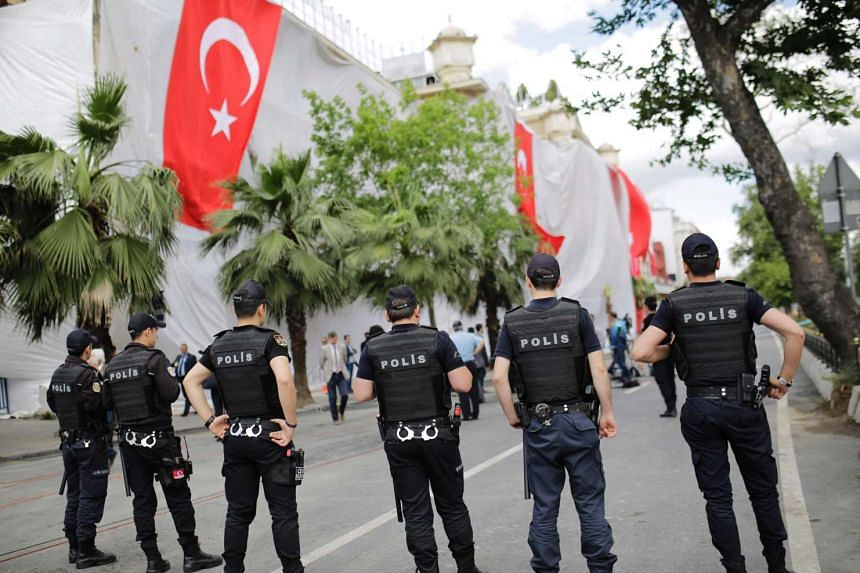 Turkish policemen stand near a hotel building a day after a bomb explosion in Vezneciler district of Istanbul on June 8, 2016.