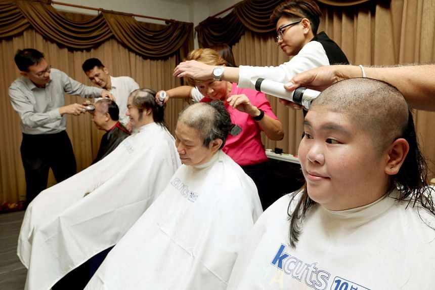 The first four shavees of the event getting their hair shaved: (from left) CabbyCare vice-chairman Ang Kim Thye, Stannley Chiok, Kirsty Foo and Josephine Kee.