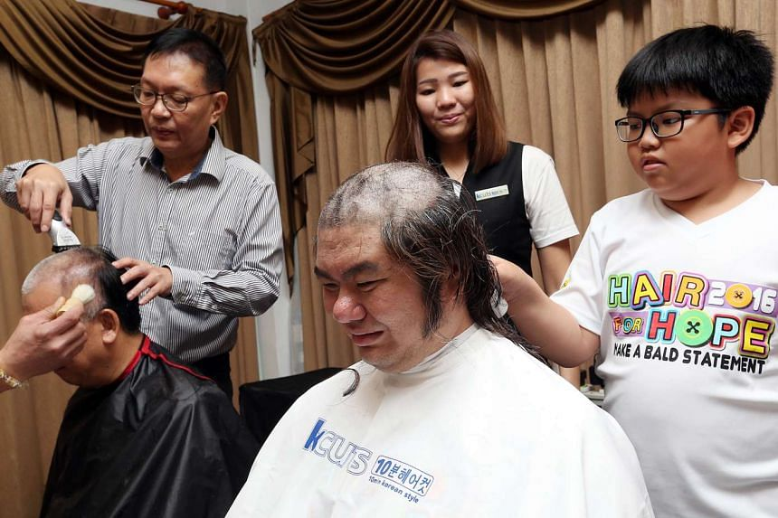 CabbyCare vice-chairman Ang Kim Thye and cabby Stannley Chiok getting their hair shaved.