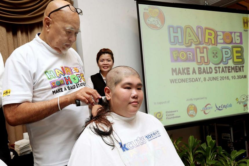 CabbyCare Charity Group Chairman, Freddie Lee, shaving the head of Josephine Kee, one of the first two female cabbies to ever participate in ComfortDelGro's Hair for Hope.