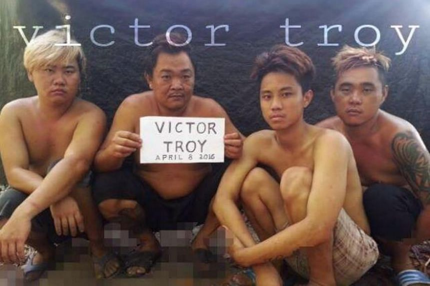 """The four kidnapped sailors. """"Victor Troy"""" in the sign refers to a Facebook account under the name """"Victor Troy Poz"""", where the image was first loaded."""