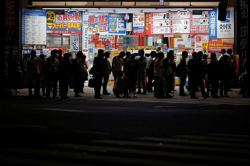 People in front of an electronics shop in Tokyo on June 7.