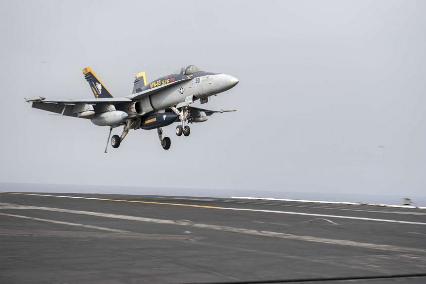 A US Navy F/A-18C Super Hornet prepares to land on the flight deck of aircraft carrier USS Harry S. Truman in the Mediterranean Sea on June 3, 2016.