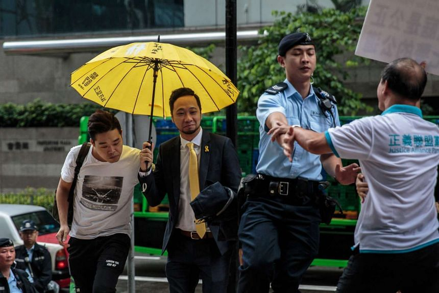 Pro-democracy activist Ken Tsang (centre) reacts as a pro-police protester shouts slogans outside the district court on June 6, 2016.
