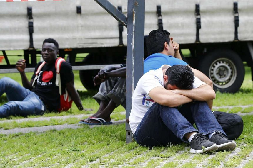 Migrants rest on the ground after exhibition halls used as refugee camps were damaged by fire in Duesseldof, Germany, June 7, 2016.