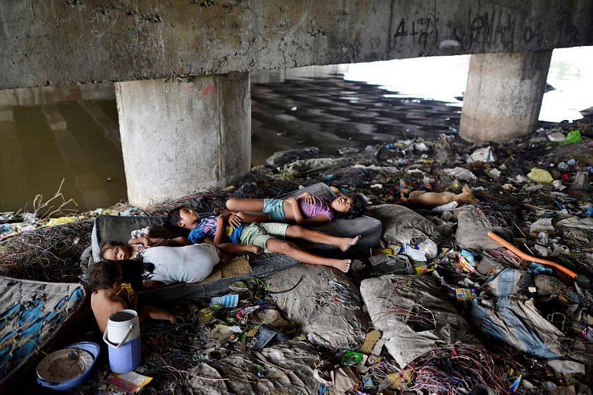 Children sleeping amidst rubbish under a bridge in Paranaque city, Manila.