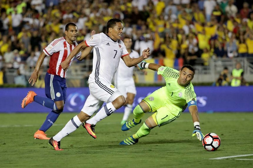Carlos Bacca (centre) of Colombia breaking past Paraguay goalkeeper Justo Villar during the second half of their Copa America match.