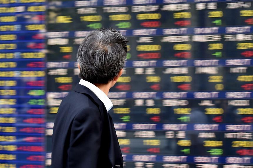 A man looking at an electronic stock board at the window of a securities company in Tokyo on June 3.